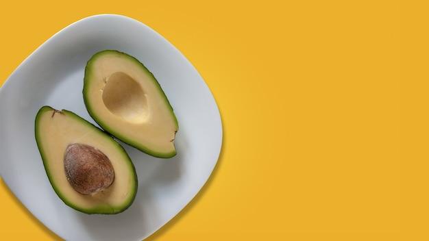 Duas partes de abacate na chapa branca. isolado em amarelo.