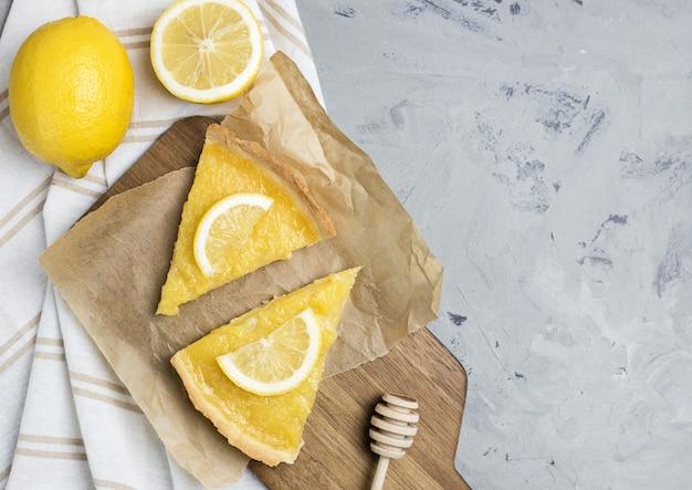 Duas partes de torta de limão com fatia de close up dos limões no fundo de pedra, copiam o espaço.