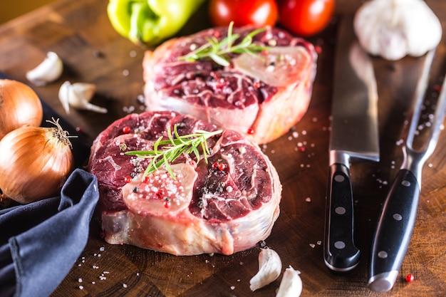 Duas peças de pernil de carne crua e ingredientes básicos em goulash cebola pimenta tomate alho e sal