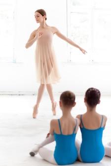 Duas pequenas bailarinas dançando com a professora pessoal de balé no estúdio de dança
