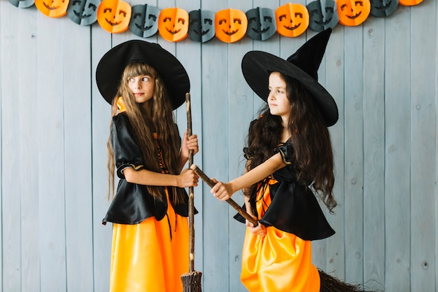 Duas pequenas bruxas com vassouras no halloween