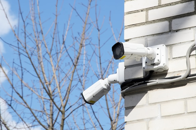 Duas pequenas câmeras cctv brancas no canto da fachada de um prédio de tijolos de vários andares.