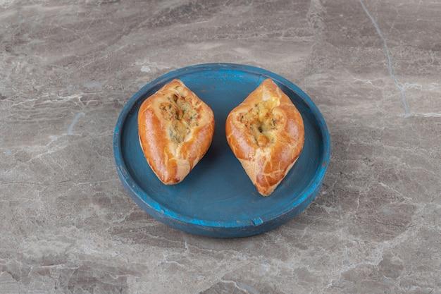 Duas pequenas porções de ervilhas turcas em uma bandeja azul na superfície de mármore