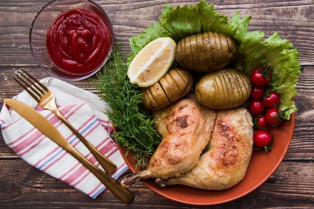Duas pernas de frango grelhado com frutas e legumes na tigela