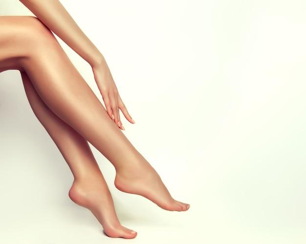 Duas pernas de mulher perfeitas tocadas por mãos finas e graciosas pernas nuas pés suaves cuidados com o corpo