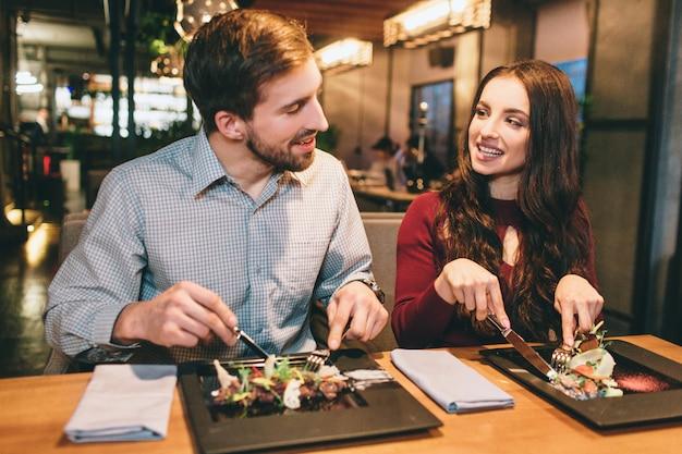 Duas pessoas adoráveis estão sentadas no restaurante e comendo saladas. eles também estão olhando um para o outro e sorrindo.