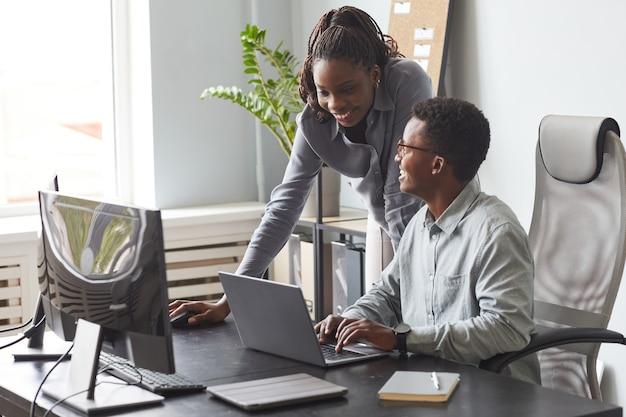 Duas pessoas afro-americanas trabalhando juntas em um escritório
