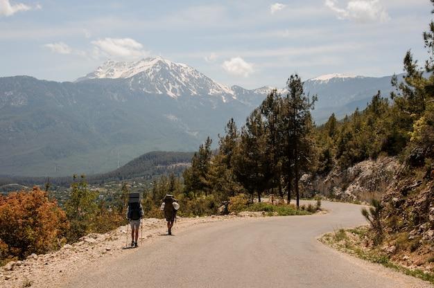 Duas pessoas andando na estrada com mochilas para caminhadas