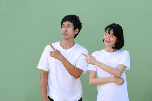 Duas pessoas asiáticas em pé e olhando o dedo apontam para a vista lateral. imagem de trajeto de recorte isolado