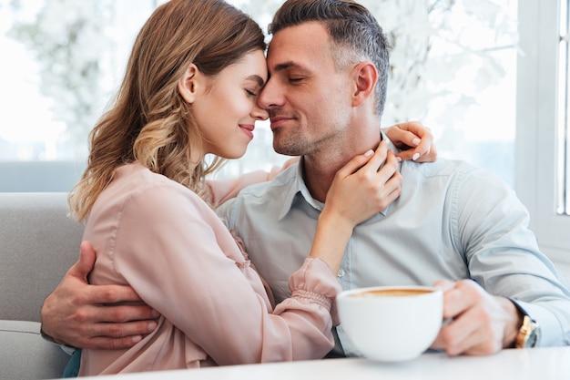 Duas pessoas bonitas, homem e mulher, abraçando e tendo prazer, enquanto relaxam juntos no restaurante em dia brilhante