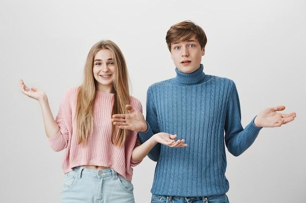 Duas pessoas confusas dando de ombros. garota e cara não sabem nada