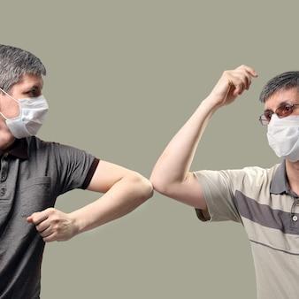 Duas pessoas cumprimentam cotoveladas em vez de apertar as mãos