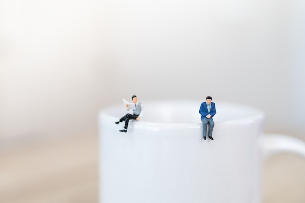 Duas pessoas de figura em miniatura de empresário em pé em cima de caneca branca xícara de café quente com distanciamento social.