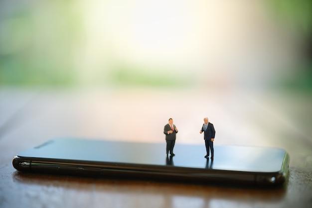 Duas pessoas de figura em miniatura do empresário em pé e se encontrando no smartphone na mesa de madeira.
