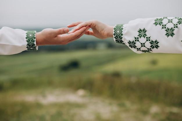 Duas pessoas de mãos dadas no prado