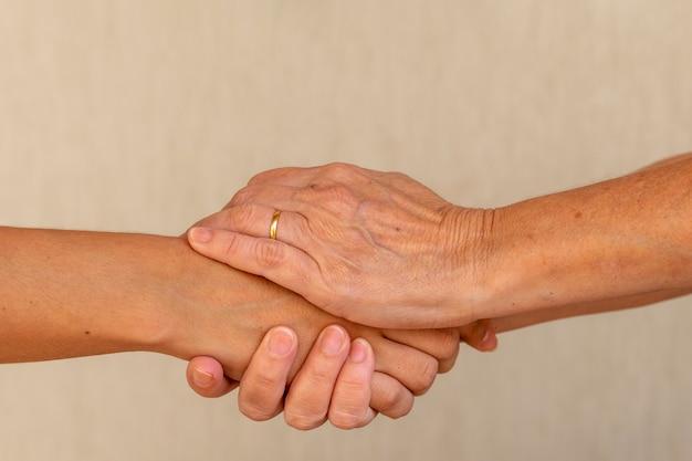 Duas pessoas de mãos dadas, uma mulher idosa e uma jovem apertando as mãos, ajudando a mão e o conceito de paz mundial com espaço de cópia