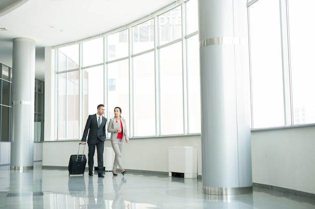 Duas pessoas de negócios, caminhando para o portão no aeroporto