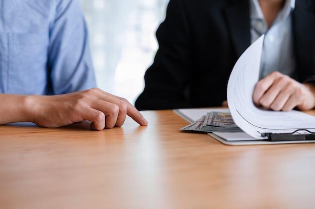 Duas pessoas de negócios recebendo suborno passando dinheiro sob folhas de documentos. conceito de corrupção de suborno