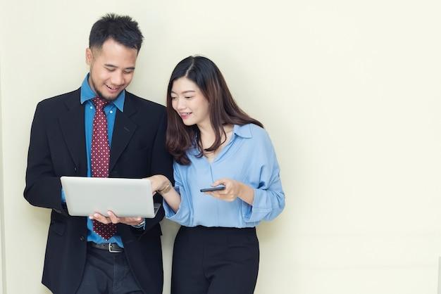 Duas pessoas de negócios usando móveis e laptop.