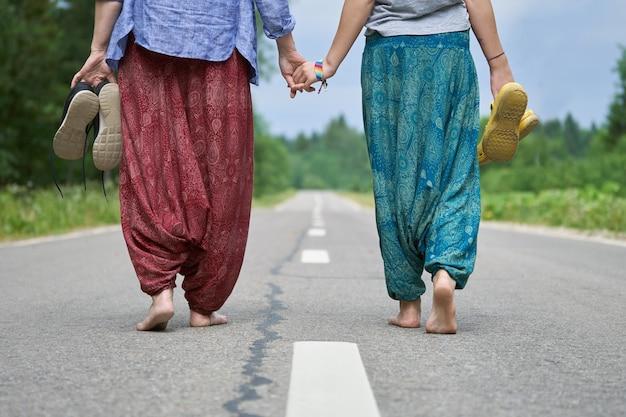 Duas pessoas descalças, vestindo calças indianas, caminhando de mãos dadas ao longo da estrada de asfalto. as linhas divisórias das estradas são visíveis entre duas pessoas. visão de baixo ângulo.