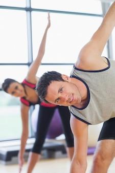 Duas pessoas desportivas, esticando as mãos na aula de ioga