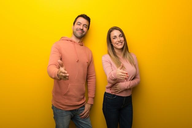 Duas pessoas em fundo amarelo apertando as mãos para fechar um bom negócio