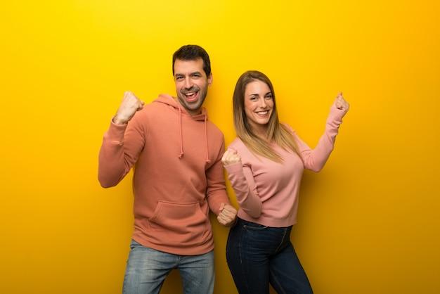 Duas pessoas em fundo amarelo comemorando uma vitória