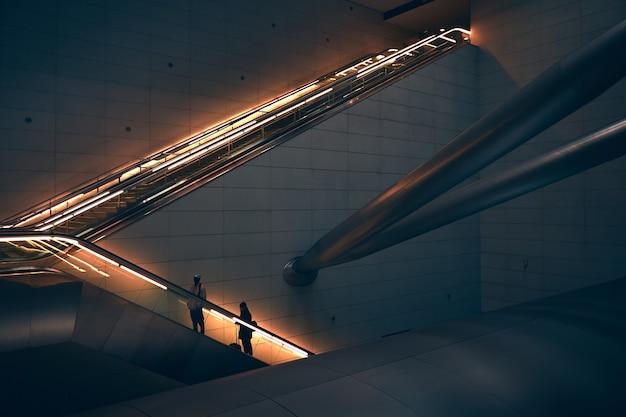 Duas pessoas em pé na escada rolante