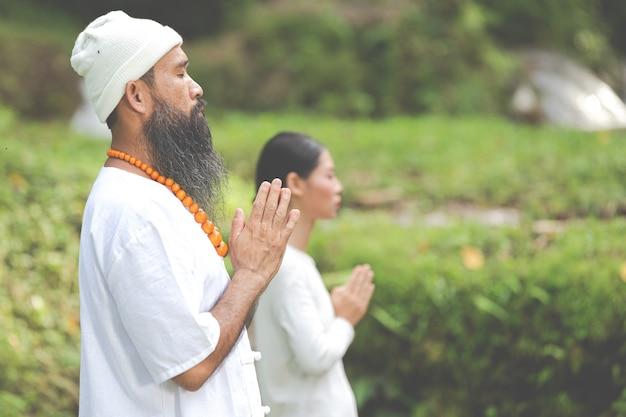 Duas pessoas em roupa branca meditando na natureza
