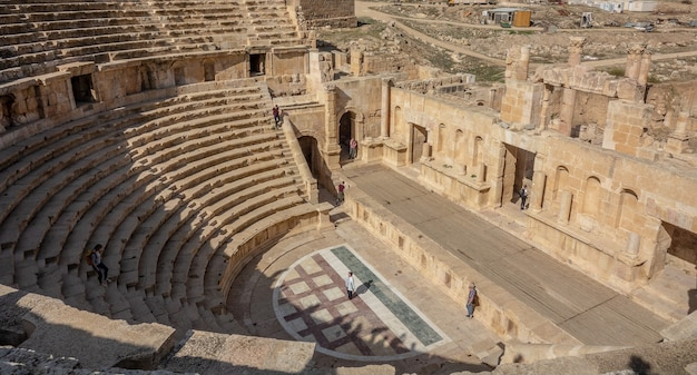 Duas pessoas em um antigo anfiteatro durante o dia