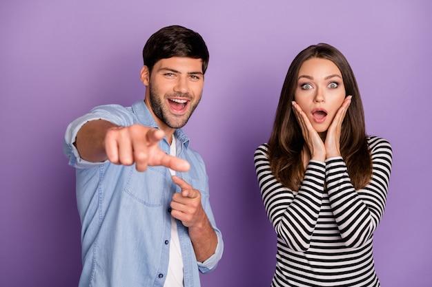 Duas pessoas engraçadas, casal de boca aberta, ouvir boas notícias direcionando o dedo à frente, use roupas elegantes e casuais isoladas na parede de cor roxa pastel