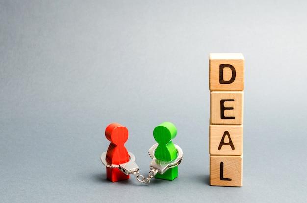 Duas pessoas estão algemadas com a palavra deal.