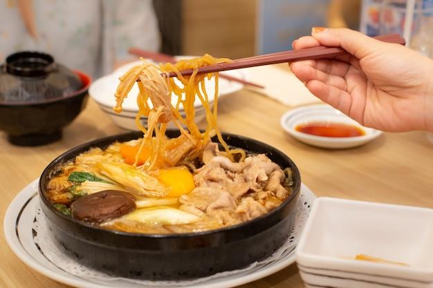 Duas pessoas estão comendo carne de porco shabu ou panela quente. tempo para a família.