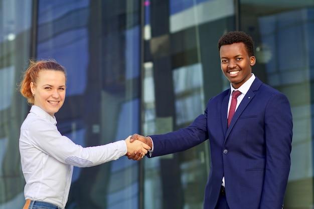 Duas pessoas felizes e sorridentes: empresário e empresária estão apertando as mãos, cumprimentando. mulher jovem europeia branca e homem afro-americano negro em traje formal ao ar livre