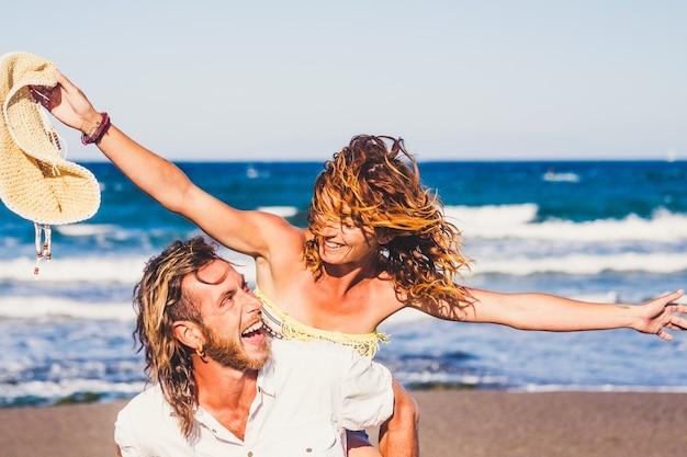 Duas pessoas felizes, se divertindo juntos e sorrindo na praia. férias ao ar livre juntos.
