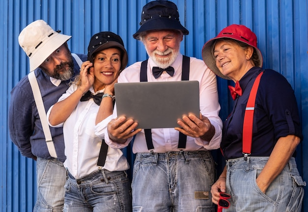 Duas pessoas idosas com filhos de meia idade em frente a uma parede azul. olhando juntos para o mesmo laptop vestidos coloridos com suspensórios e gravata borboleta.