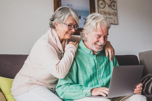 Duas pessoas idosas e maduras em casa usando o tablet juntas no sofá. senior use laptop se divertindo e gostando de olhar para ele. conceito de lazer e tempo livre