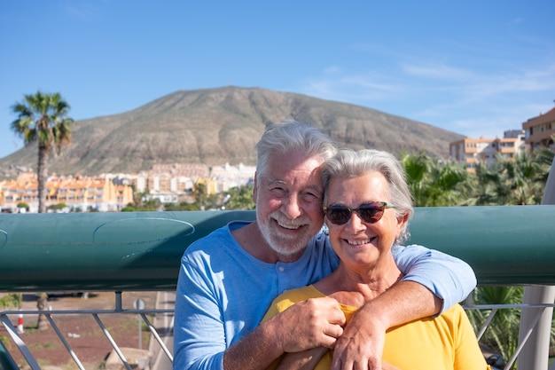 Duas pessoas idosas sorridentes abraçaram-se em uma ponte sobre o tráfego da cidade. aposentados agradáveis e serenos
