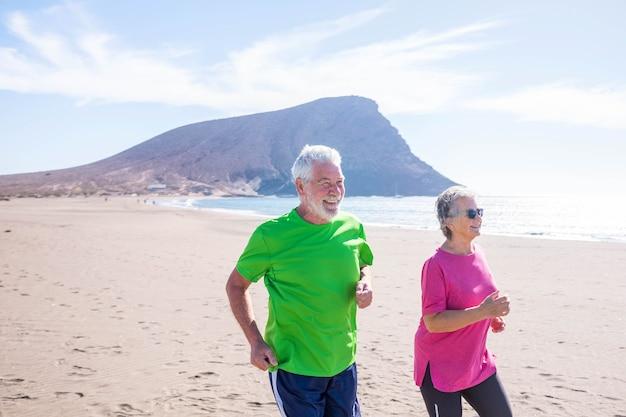 Duas pessoas maduras fazendo exercícios e esportes juntas na praia, sorrindo e rindo - idosos ativos fazendo jogging e correndo para ficarem saudáveis e em forma