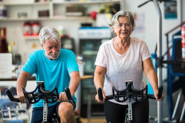 Duas pessoas maduras ou idosos ativos fazendo exercícios na academia andando de bicicleta dentro de casa para serem saudáveis - dois aposentados felizes com estilo de vida saudável