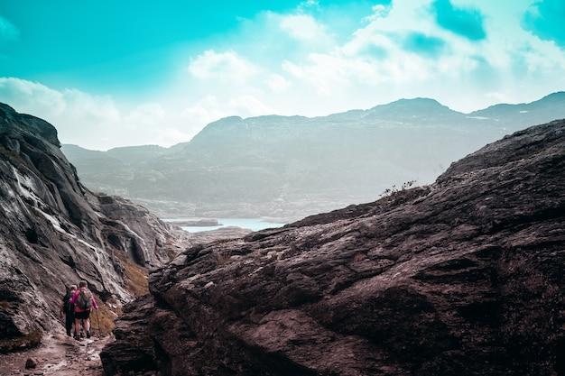 Duas pessoas pequenas contra as majestosas montanhas norueguesas