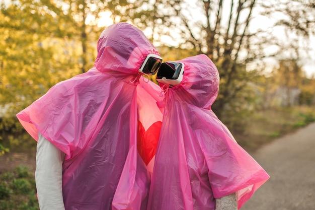 Duas pessoas se olhando romanticamente em capas de chuva de plástico rosa e fones de ouvido de realidade virtual
