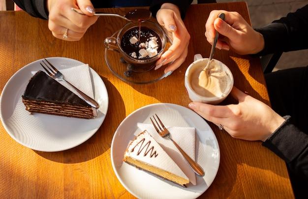 Duas pessoas segurando bolos frescos, café com creme e chocolate quente na mesa de um café