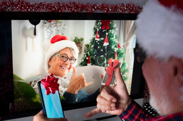 Duas pessoas sênior em videochamada devido ao bloqueio sorrindo felizes mostrando o presente de natal. em casa com computador e aparelhos tecnológicos
