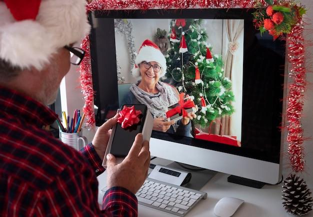 Duas pessoas sêniors sorridentes com chapéus de papai noel em videochamada com computador abrindo juntos os presentes de natal. velhos aposentados ativos viciados em novas tecnologias. bloqueio devido ao coronavírus covid-19