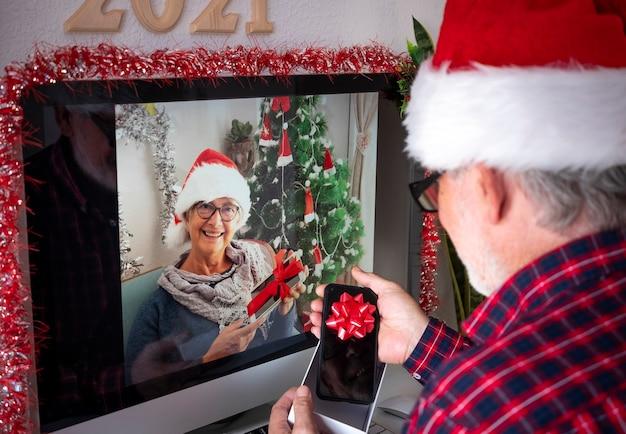 Duas pessoas sêniors sorridentes com chapéus de papai noel em videochamada com computador abrindo os presentes de natal. velhos aposentados ativos viciados em novas tecnologias. bloqueio devido ao coronavírus covid-19