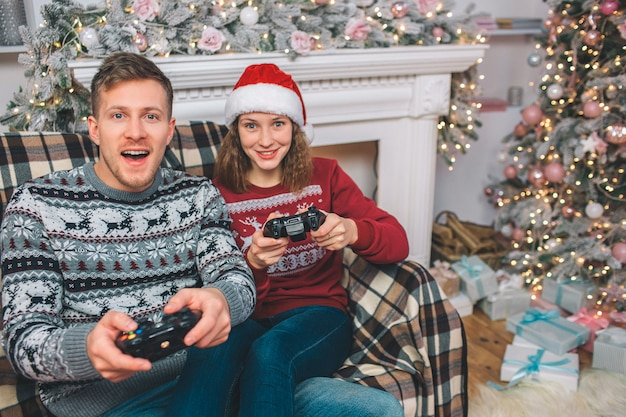 Duas pessoas sentadas e jogando. thay tem gamepads nas mãos. jovem e mulher estão animado. eles apertam botões e brincam com emoção no quarto decorado.
