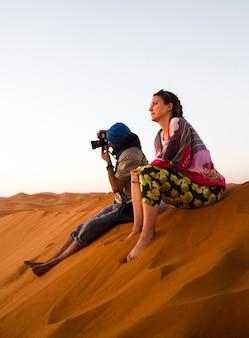 Duas pessoas sentadas em cima da duna tirando fotos