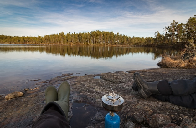 Duas pessoas sentadas na beira do lago fazendo café em um fogão de acampamento, floresta de pinheiros no deserto da noruega
