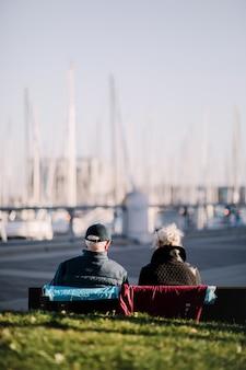 Duas pessoas sentadas no banco durante o dia
